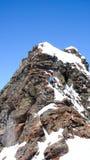 上升到与他的滑雪的一个被暴露的岩石山顶的男性偏远地区滑雪者被束缚到他的背包 免版税库存照片
