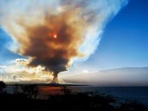 上升到与通过发光在海岛的太阳的天空的烟 库存照片