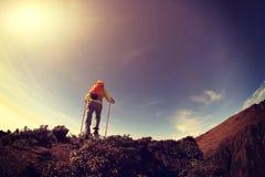 上升到山峰的妇女背包徒步旅行者 免版税库存图片