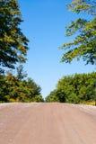 上升反对树和天空的空的土路 库存图片