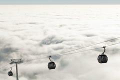 上升和下降山在一个冬季体育度假区的新的缆车在一多云天 免版税库存照片
