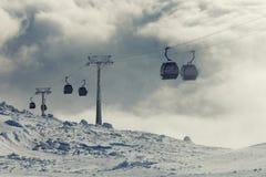 上升和下降高在山的缆车客舱在一个冬季体育度假区在一多云天 免版税库存图片