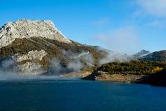 上升在一个多山风景的一个水库的薄雾 库存照片