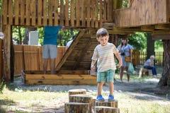 上升在一个木操场的小男孩在绳索公园 户外孩子戏剧温暖的晴朗的夏日 免版税库存照片