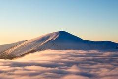 上升在一朵蓬松云彩,寒冷上的积雪覆盖的山,冷淡 免版税库存图片