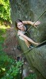 上升在一条岩石墙壁绳索的愉快的妇女, bouldering 免版税库存图片
