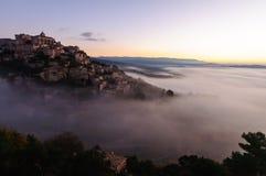 上升在云彩外面的小山村庄 免版税库存照片