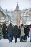上升在传统圣诞节市场上的Schimmelturm 在街道、圣诞树和报亭,落的雪上的人们 图库摄影