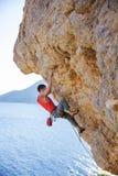上升在伸出的峭壁的年轻人主角 免版税库存照片