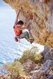 上升在伸出的峭壁的年轻人主角 库存照片
