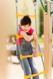 上升在儿童操场的愉快的小女孩 免版税库存图片