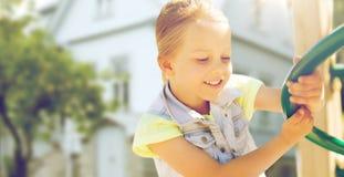 上升在儿童操场的愉快的小女孩 库存图片