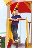 上升在儿童操场的愉快的小男孩 图库摄影
