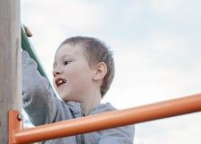上升在儿童操场的男孩户外 获得幼儿园的孩子在操场的乐趣 使用在儿童操场的孩子 库存照片