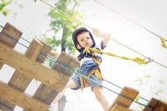 上升在冒险公园的孩子 男孩喜欢上升在绳索 图库摄影