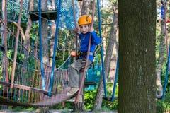 上升在冒险公园,绳索公园的男孩 免版税库存照片