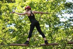 上升在冒险安全设备的绳索公园的可爱的妇女 免版税库存图片