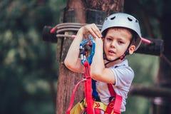 上升在冒险有盔甲的活动公园的小男孩 免版税库存照片
