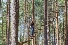 上升在冒险绳索公园的年轻勇敢的妇女 免版税库存图片