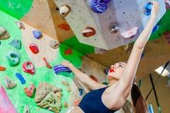 上升在墙壁上的性妇女在一个室外上升的中心 图库摄影