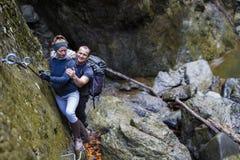 上升在安全的远足者夫妇在上的一道峡谷缚住 免版税图库摄影