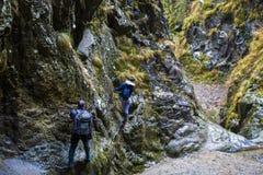 上升在安全的远足者夫妇在上的一道峡谷缚住 图库摄影