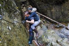 上升在安全的远足者夫妇在上的一道峡谷缚住 库存图片