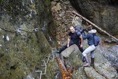 上升在安全的远足者夫妇在上的一道峡谷缚住 库存照片