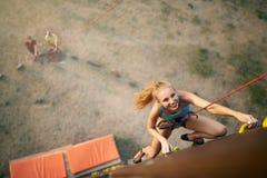 上升在岩石人为墙壁上的美丽的年轻坚强的妇女在夏天,顶视图 在系住的鞔具保险的登山人 免版税库存图片