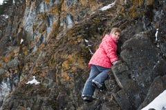 女孩攀登岩石 库存照片