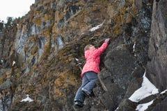 女孩攀登岩石 免版税库存图片