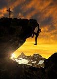 上升在岩石的女孩Silhoutte在日落 免版税库存图片