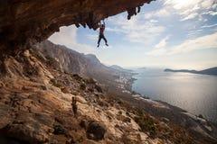 上升在岩石的攀岩运动员在日落 免版税库存照片