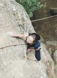 上升在岩石的运动的妇女 免版税库存照片