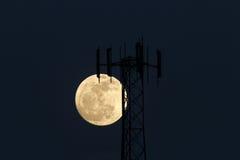 上升在手机塔后的满月 免版税库存图片