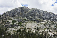 上升在森林上的花岗岩山 库存照片