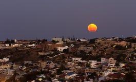 上升在沿海城市和家的月亮 免版税库存照片