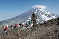 上升在火山上面的大小组远足者  免版税库存图片