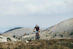 去上升在的年轻运动员骑自行车者mountainbiker体育骑自行车 免版税图库摄影