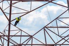 上升在高危险输电线的工作者 库存图片