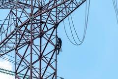 上升在高危险输电线的工作者 图库摄影