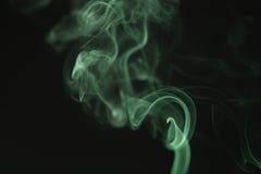 上升在黑背景的奥秘波浪绿色烟 库存照片