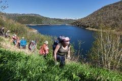 上升沿小山,山湖峭壁岸倾斜的小组游人  免版税库存图片
