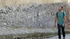 上升沿高石墙的年轻男性游人看好奇地在去 股票录像