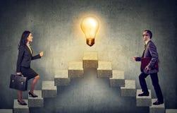 上升的商人提高与想法电灯泡的一架楼梯事业梯子在上面 免版税库存照片