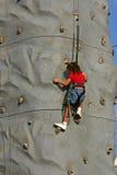 上升的女孩岩石墙壁 图库摄影