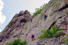 上升的结岩石系住二 一个小组年轻攀岩运动员攀登垂直的花岗岩岩石 极其体育运动 登山家训练  免版税库存图片