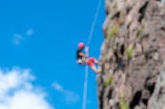 上升的结岩石系住二 登山人的被弄脏的图在一个垂直的岩石 模糊的五颜六色的bokeh背景 抽象图象 库存图片