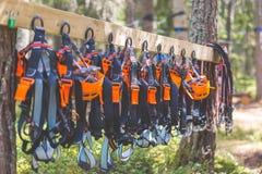 上升的齿轮设备-橙色盔甲鞔具邮编线垂悬在委员会的安全设备 旅游夏时冒险公园 免版税库存照片