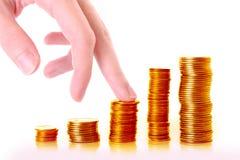 上升硬币栈的手指 免版税库存照片